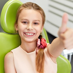 Smiling young girl in dental chair giving thumbs up