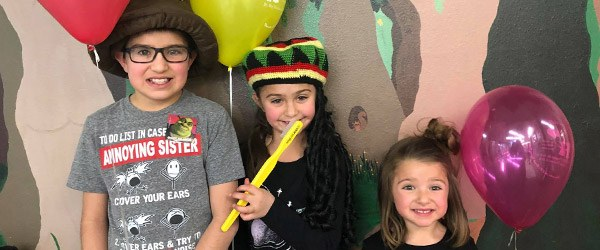 Three kids wearing fun hats and holding props