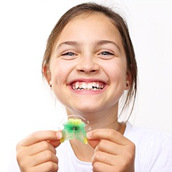 Smiling girl holding oral appliance