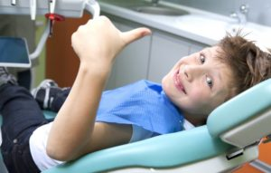 A child giving a thumbs up at his dental appointment.