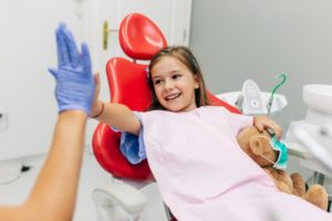 Young girl high-fiving her Casper children's dentist during first appointment