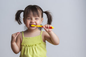Little girl brushing teeth as recommended by Casper children's dentist