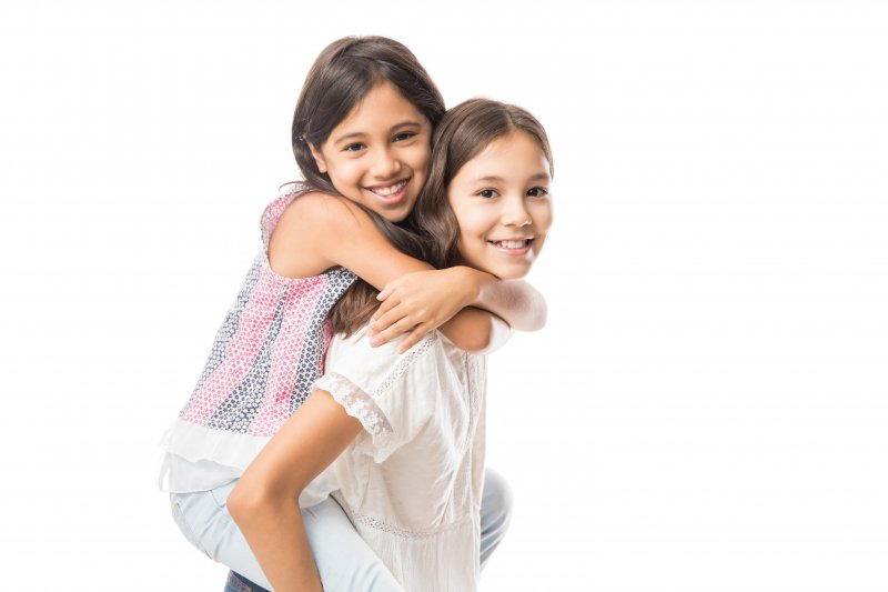 two young girls smiling after receiving dental sealants in Casper